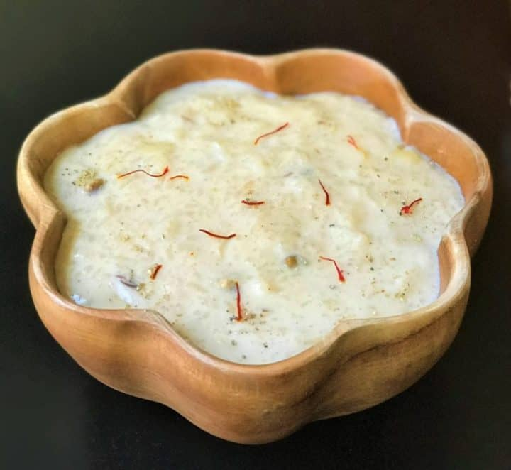 Kheer made in instant pot served in a wooden bowl.
