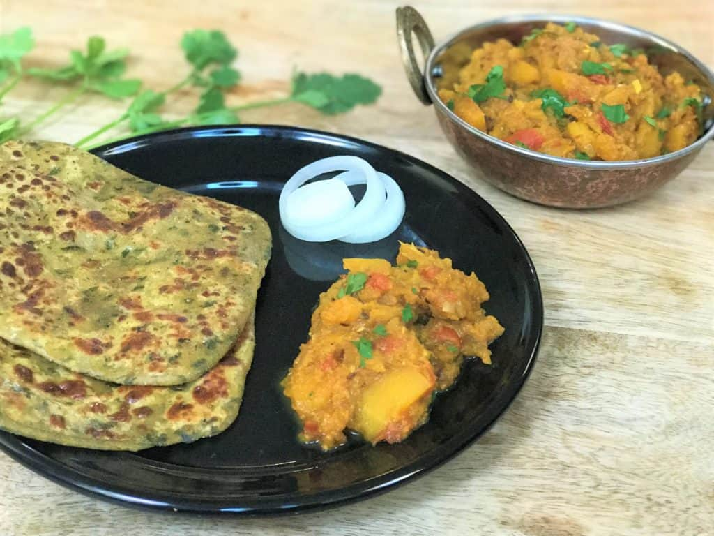 Pumpkin curry made in pressure cooker served in a black plate with two parathas and onions.