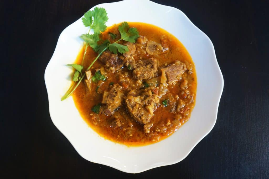 Goat Curry or Mutton Masala in the Instant Pot or Pressure Cooker. Tender meat cooked in an onion tomato gravy with aromatic whole spices