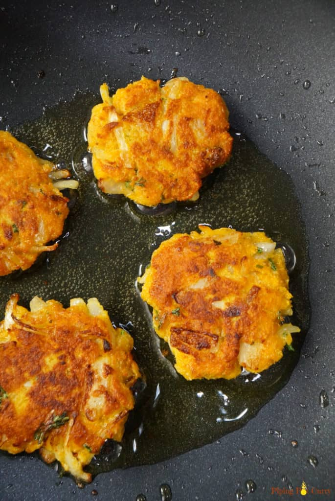 Four Vegan Chickpea Squash Fritters - Frying in a pan