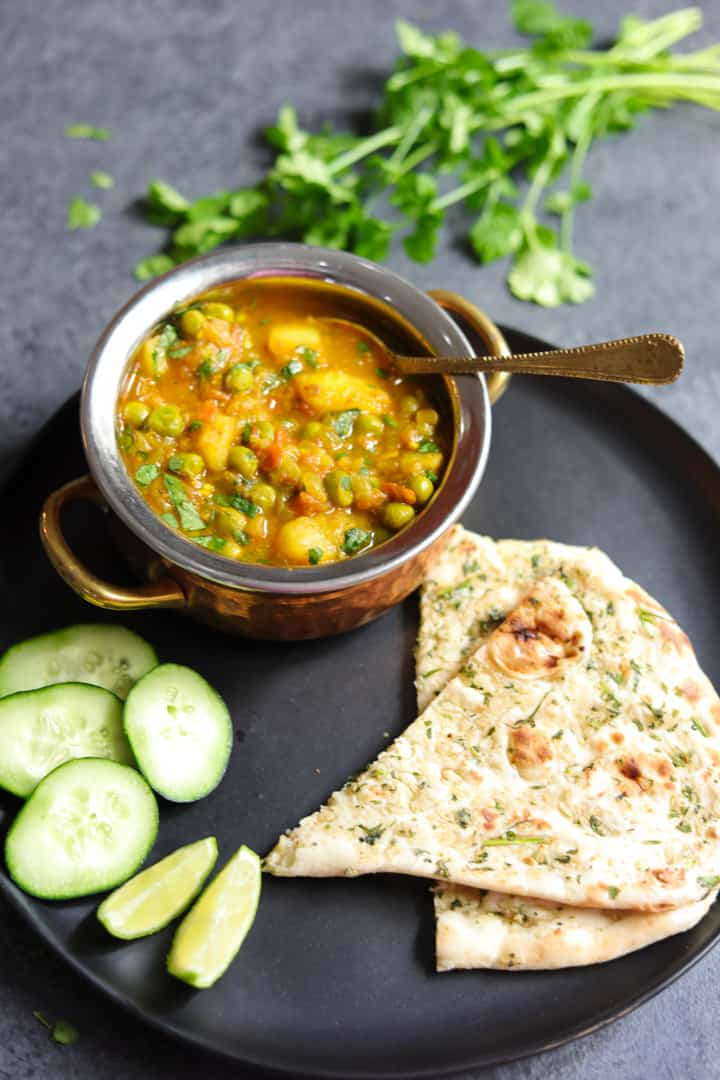 Aloo Matar made in instant pot served in a bowl, with naan bread on the side