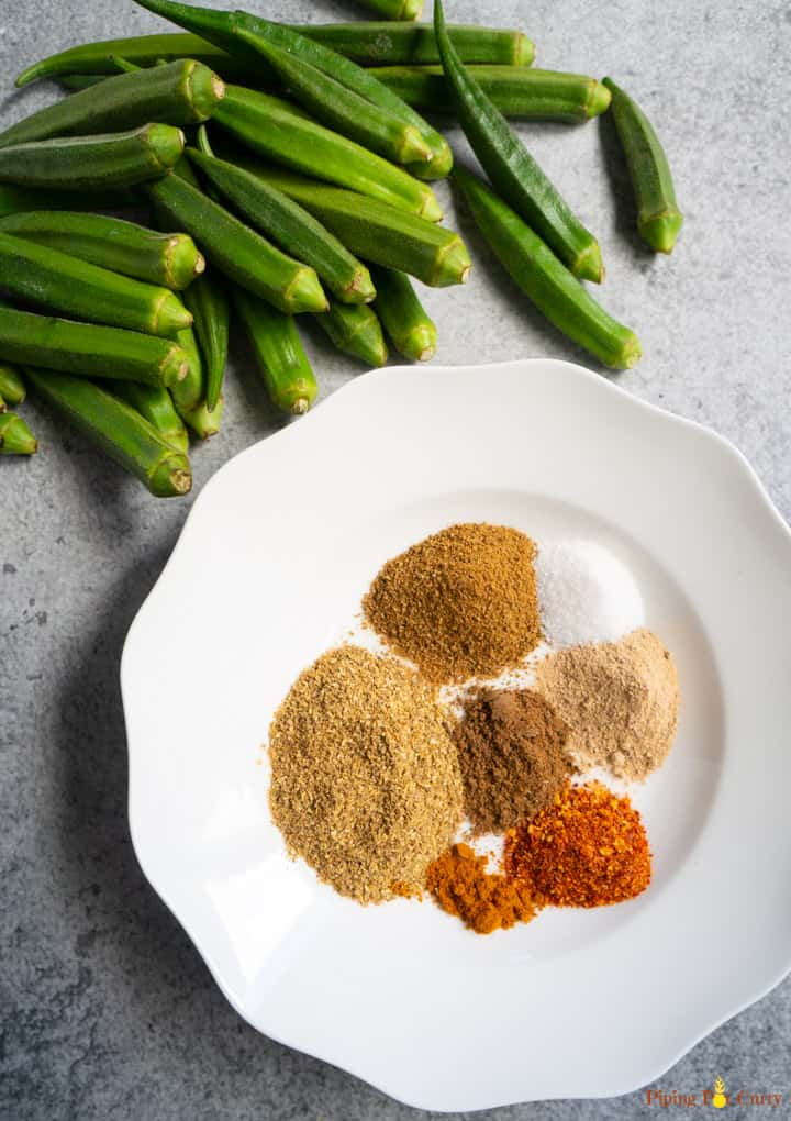 Variety of spices in a white plate to be mixed and stuffed in the okra to make stuffed okra