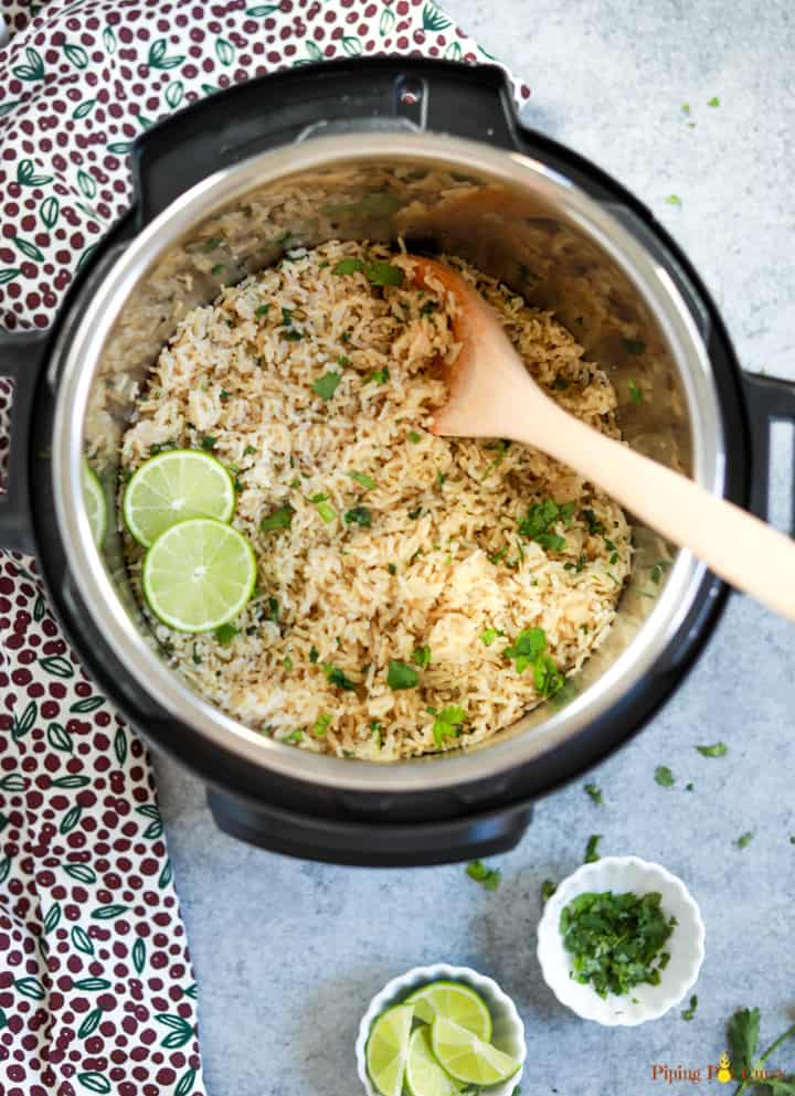 Cilantro Lime Brown Rice cooked in the instant pot, with a ladle and some lime and cilantro in small white bowls