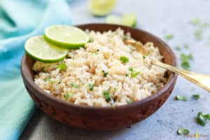 Pressure Cooker Cilantro Lime Brown Rice served in a brown bowl with lime slices and a spoon