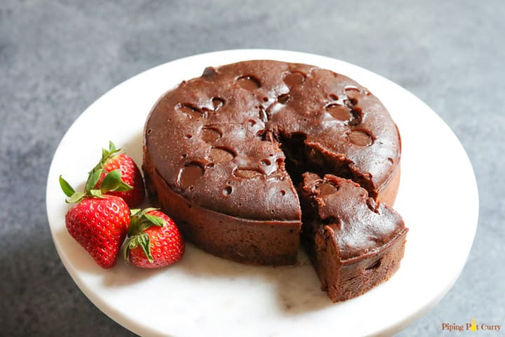 A whole brownie cake made in the instant pot, with a cut out piece and three strawberries