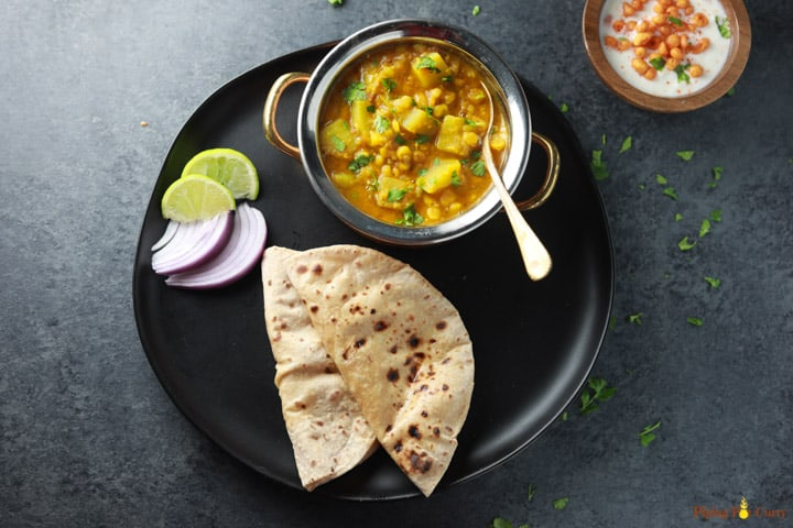 Lauki Chana Dal served with roti and onions, lime.