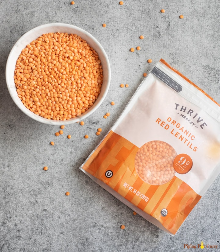 Red lentils in a bowl along with a packet of red lentils from Thrive Market