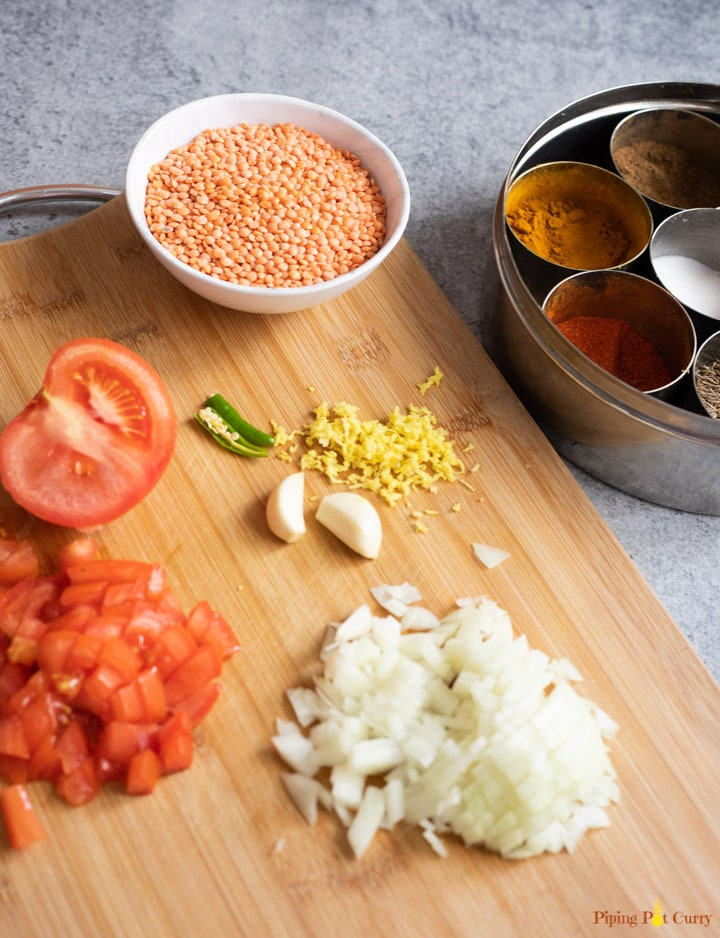Ingredients to cook dal - onions, tomatoes, ginger, garlic, spices, red lentils