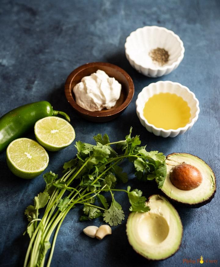 Ingredients such as avocado, jalapeño, cilantro, garlic, lime, salt, pepper