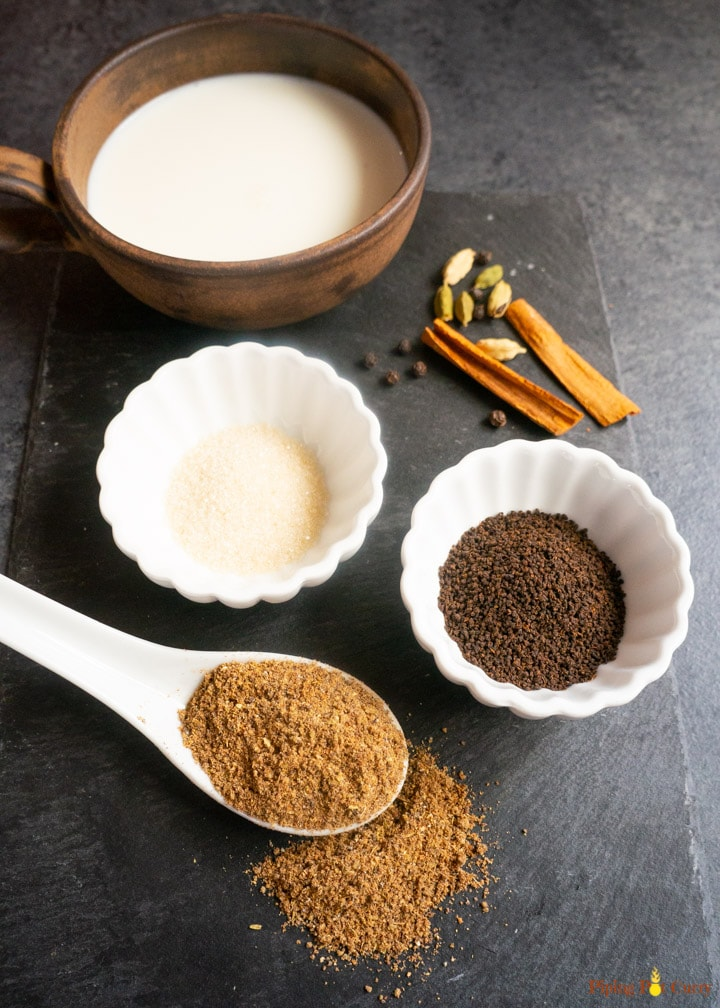 Ingredients to make masala tea. Masala tea powder, tea leaves, sugar, spices, milk