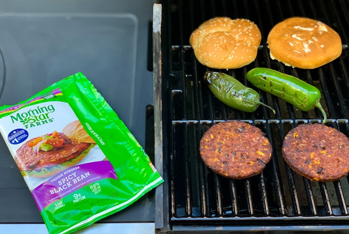 Morning star black bean burgers on a grill along with a bun and jalapeños
