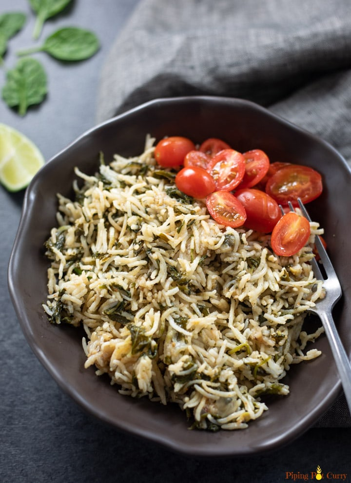 Palak Rice served in a bowl along with cherry tomatoes