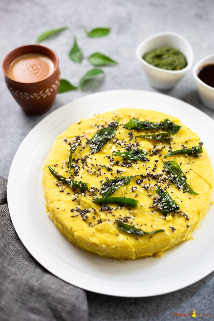 Khaman Dhokla garnished with tempering of curry leaves, along with chai and chutney.