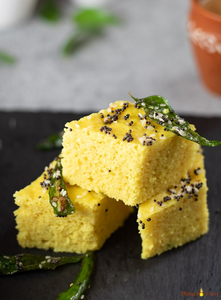 Khaman Dhokla with tempered with green chili and curry leaves stacked.