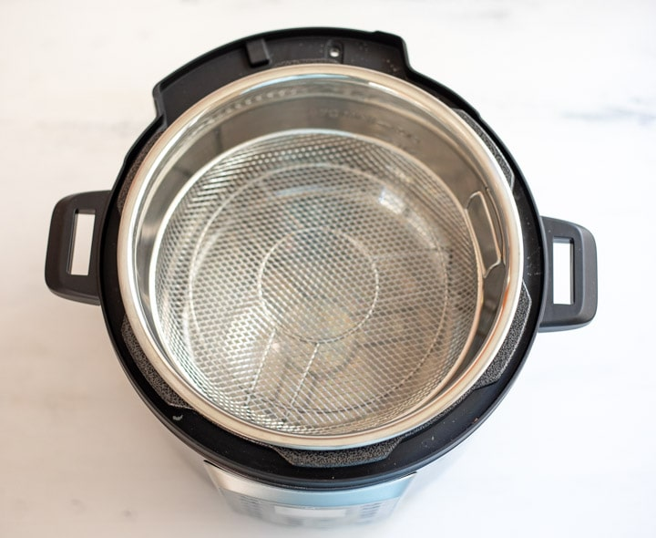Pressure cooker with a trivet and a mesh basket on the trivet