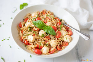 Caprese Orzo Pasta Salad in a white bowl garnished with basil