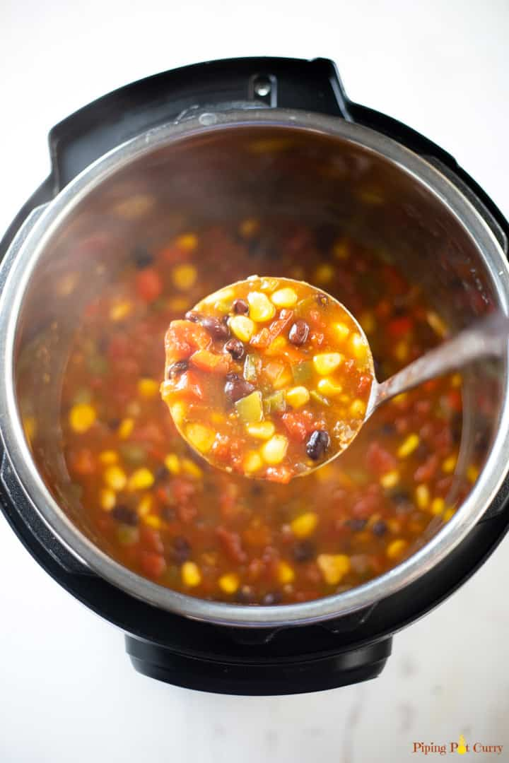 A ladle full of delicious taco soup with black beans, corn and tomatoes